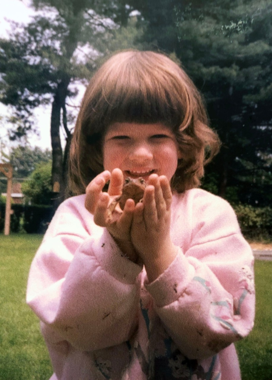 Photo of Stephanie as a young child holding a large frog in both of her hands and smiling with joy.